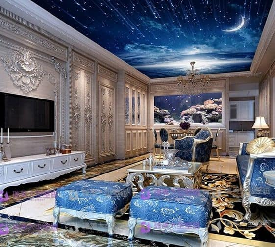 Deluxe living room with meteor shower tray ceiling and ornate walls mounted with a television. It is filled with stylish coffee table and elegant sofa with matching stools.