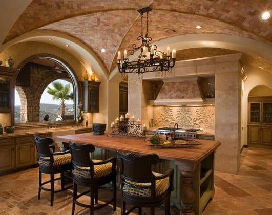 Mediterranean kitchen with fluted dome ceiling, candle chandelier, arched windows, and a base cabinet island with wood surface and counter stools.