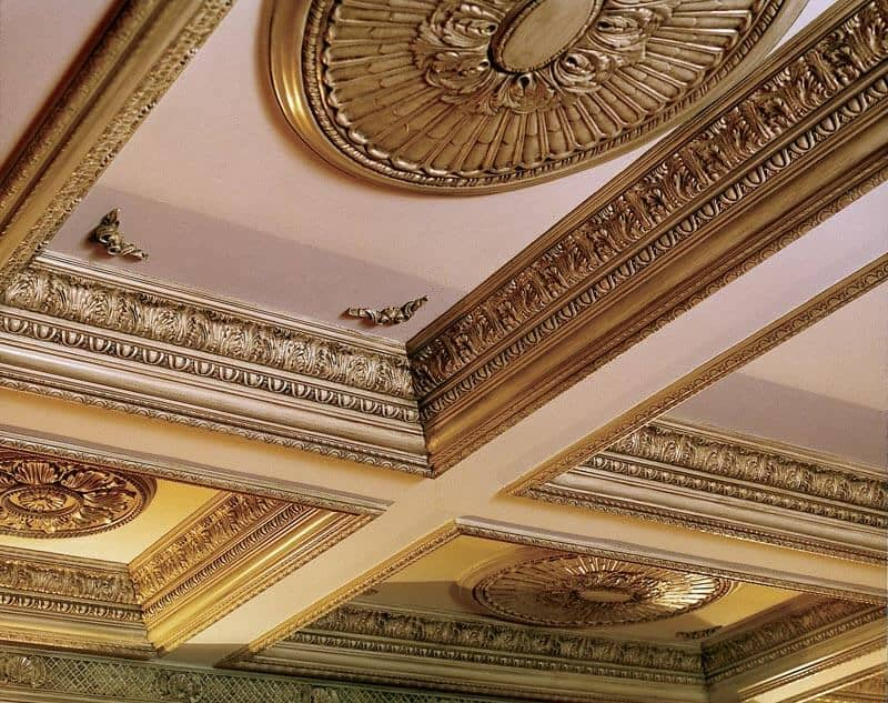 Another close up of an ornate coffered ceiling with gorgeous gilded crown molding and accents. The center of each panel has an ornate disc decoration.