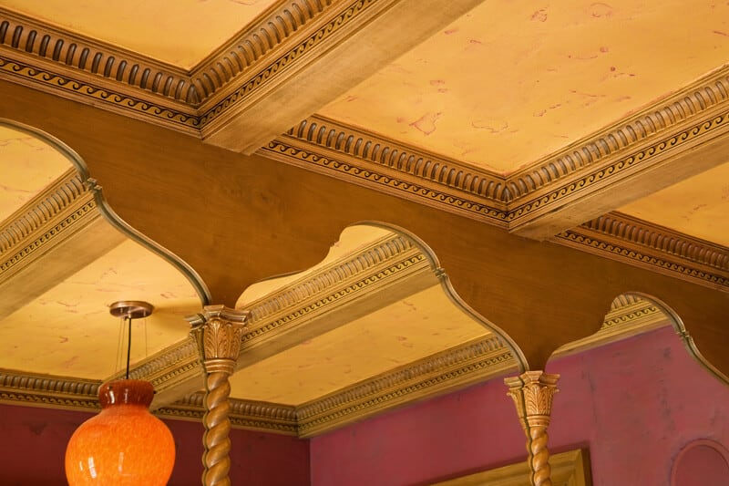 A close up of a residential coffered ceiling shows the gorgeous woodwork and tiny detailed carvings in the beams cross-sectioning the room.