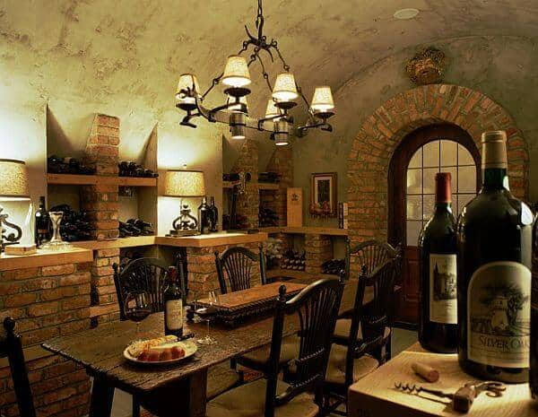 A rustic old-world style wine cellar with a long dining table in the center and a frosted-glass door leading out into the main part of the home.