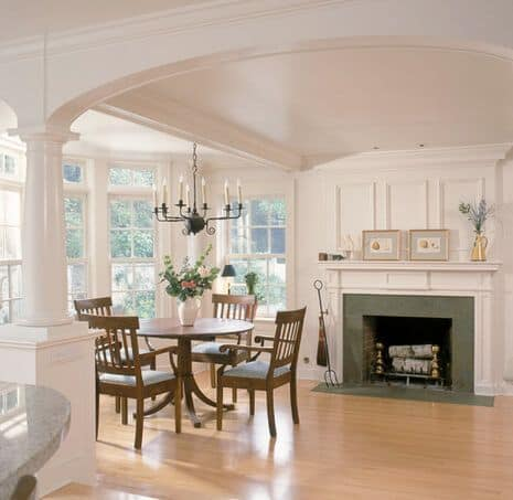 A round dining nook lighted by a glamorous chandelier and is near the fireplace.