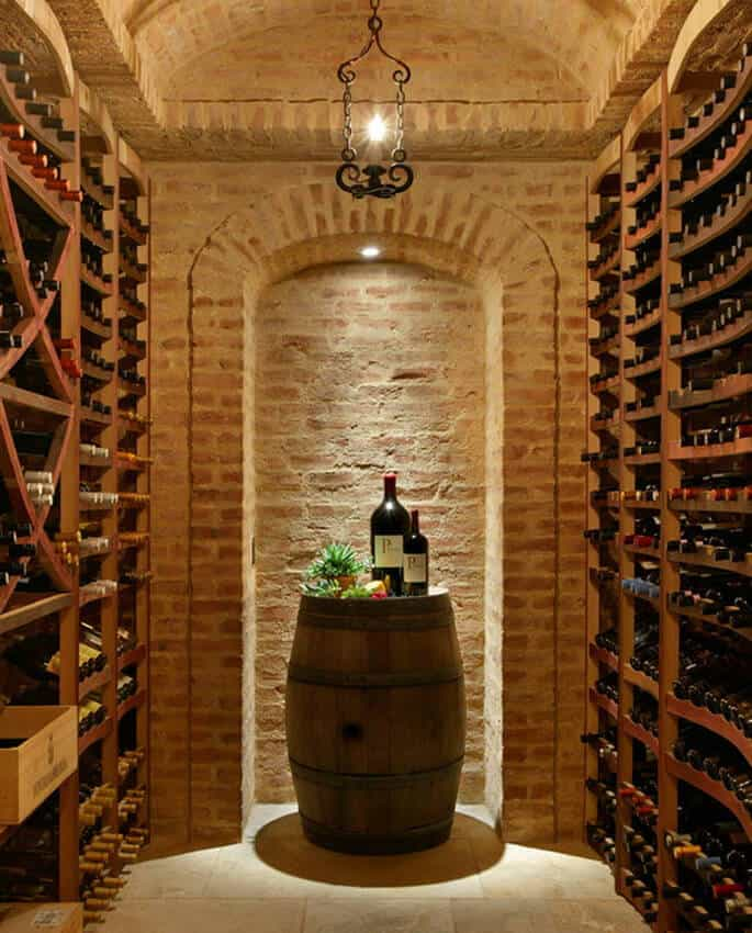 A small wine cellar with a barrel tasting table on the far wall. The brick walls are faded in spots, adding visual interest.