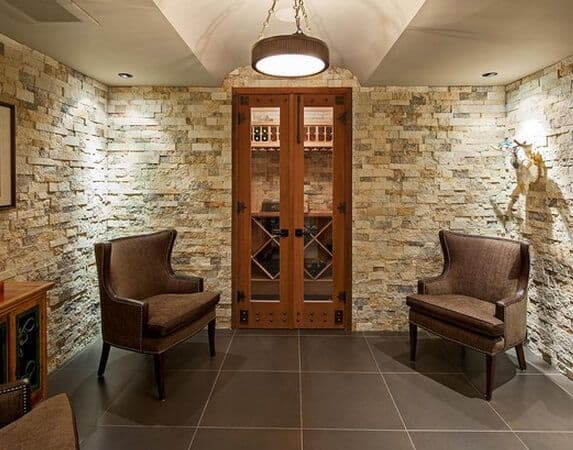 A small wine room surrounded by bricks along with a simple wine storage cabinet on the far wall and two wingback chairs on each side.