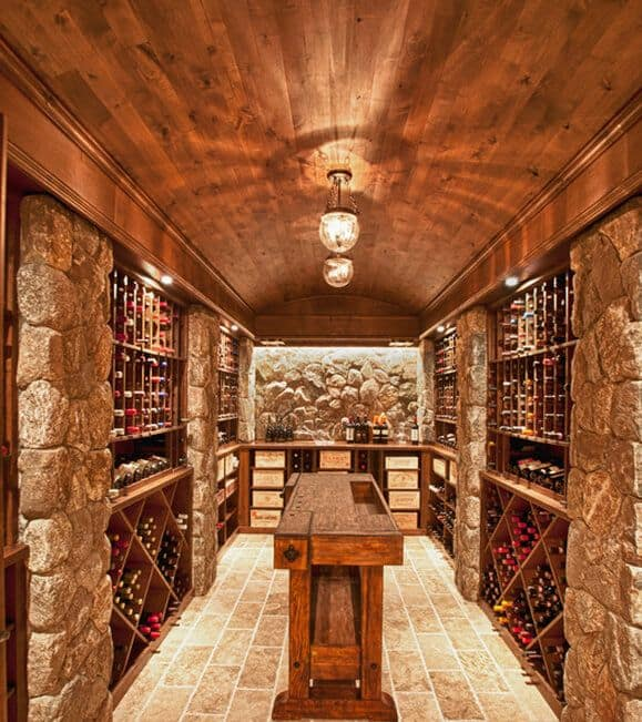 A rustic wood wine cellar accented with stone pillars and wall features extensive racks on the left and right side of the room. It has a wooden tasting bar at the center.