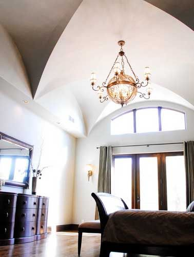 This bedroom has a steep, soaring groin vault and an orb-like chandelier above the three glass doors.