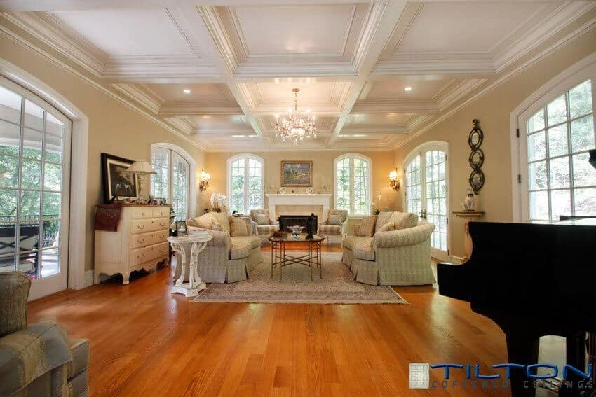 The white square coffered ceiling above the traditionally designed living room is warmed by the red hues of the hardwood flooring.