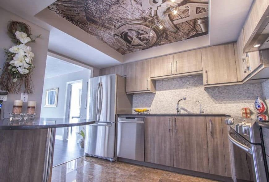 This modern kitchen in light gray and stainless steel gets a boost of personality: the ceiling has a map with an antique compass and a sextant in the tray ceiling.