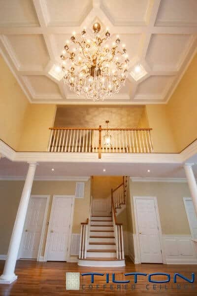 The coffered ceiling has a variety of shapes that surround an enormous, grand chandelier.