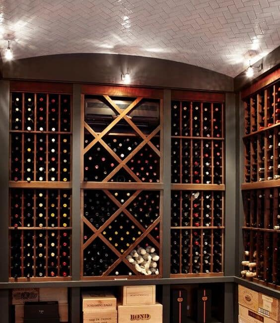 A wine cellar filled with wooden racks both of vertical design and arranged in a diamond pattern. It also features a white herringbone subway tile ceiling.