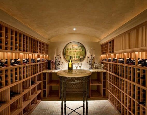 A barrel-vaulted wine cellar with textured walls and light wood wine racks on each side of the walls. It has a marble countertop in the center facing a small round tasting table.