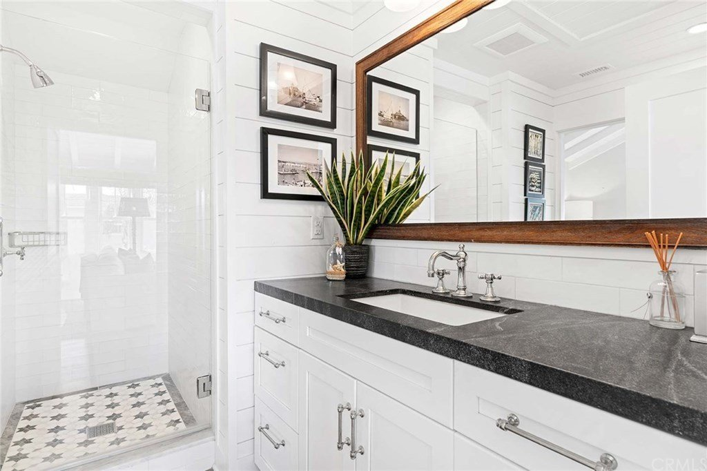 Black granite countertop contrasts the white shiplap walls and sink vanity cabinets in this cottage bathroom. This is filled with a walk-in shower and black framed artworks along with a rectangular mirror that creates a larger visual space in the room.