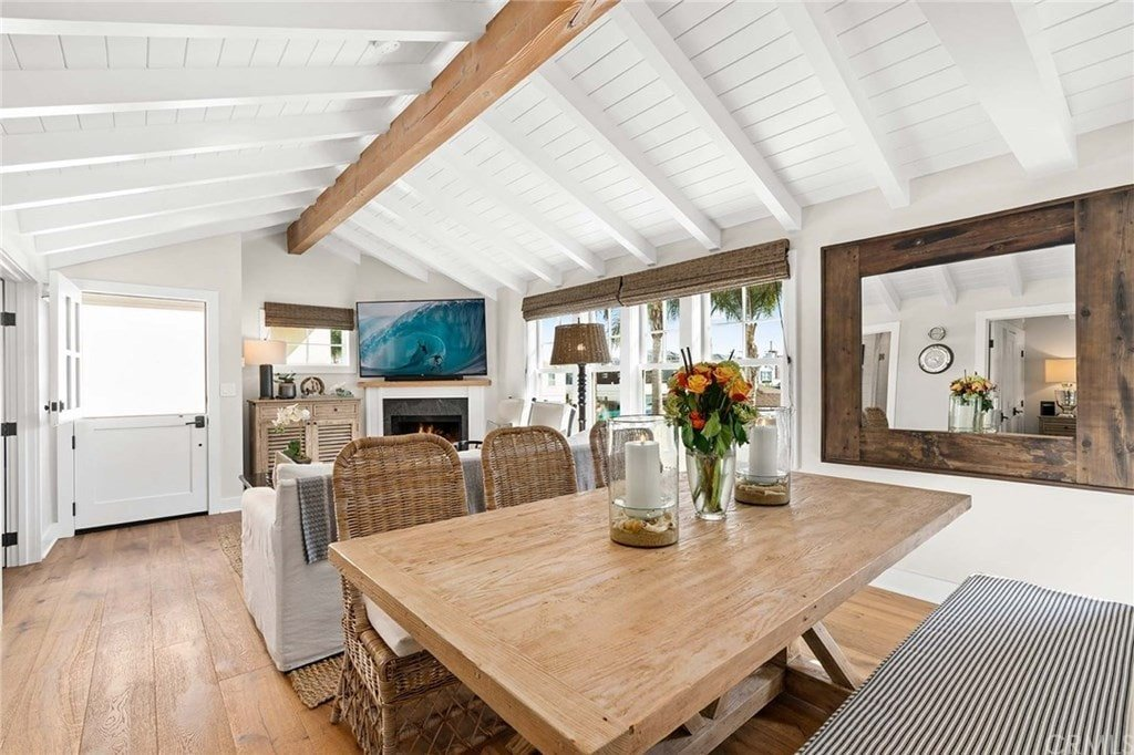 Cottage dining area on an open concept house featuring a wooden dining table flanked by wicker chairs and a striped cushioned bench. A large wooden framed mirror stands out against the white walls.