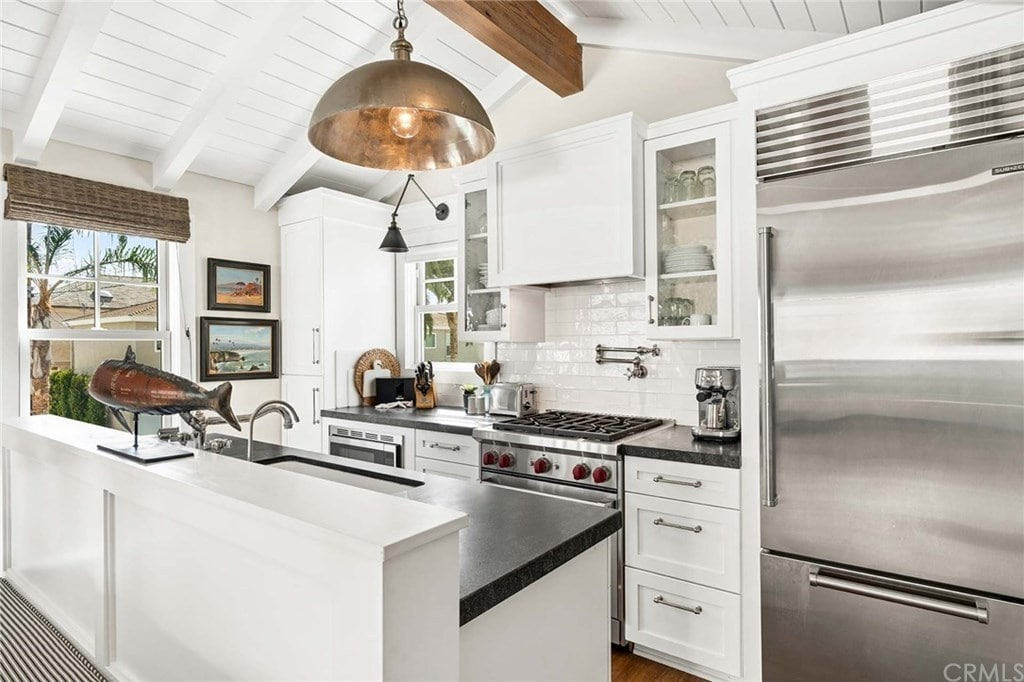 This kitchen offers pristine white walls and shiplap ceiling contrasted by a large wood beam. It is equipped with stainless steel appliances and an undermount sink fitted on the kitchen bar that's illuminated by an oversized copper pendant.