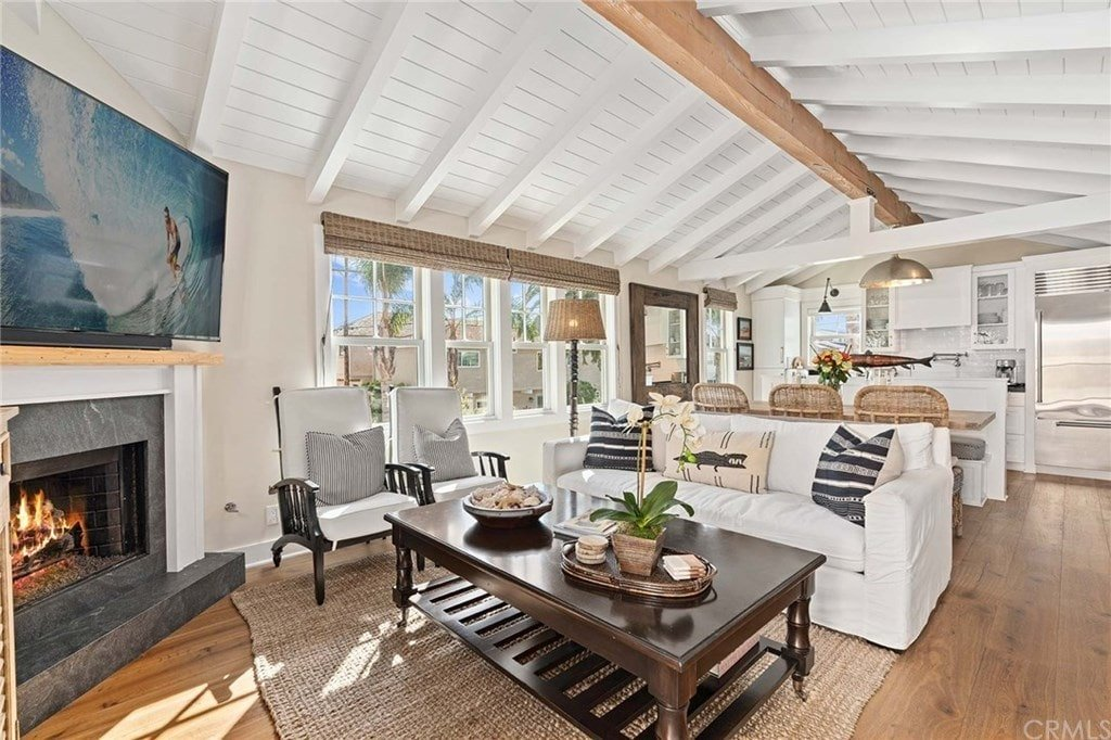 This cottage living room showcases a cathedral ceiling with exposed beams in white and natural wood matching with the wide plank flooring. It is furnished with cozy seats and a dark wood coffee table over a jute rug seated across the corner fireplace.