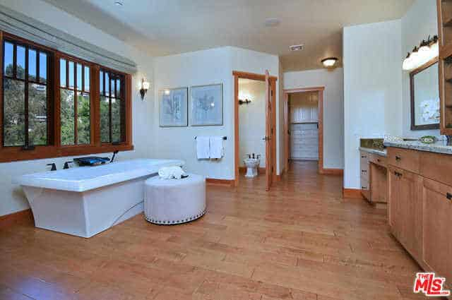 This is a spacious Craftsman-Style bathroom with floor tiles that mimic the wooden hues of the vanity area drawers and cabinets. This wooden element is also present in the window frame of the French windows above the elegant bathtub.
