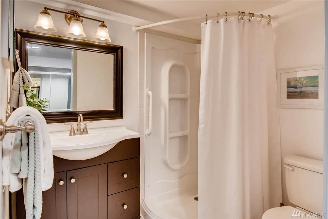 The quaint shower area of this Craftsman-Style bathroom is separated from the rest of the room by a white shower curtain that matches the white walls and white tray ceiling. An elegantly framed mirror is mounted above the brass faucet of the vanity area with dark wood cabinets and drawers.