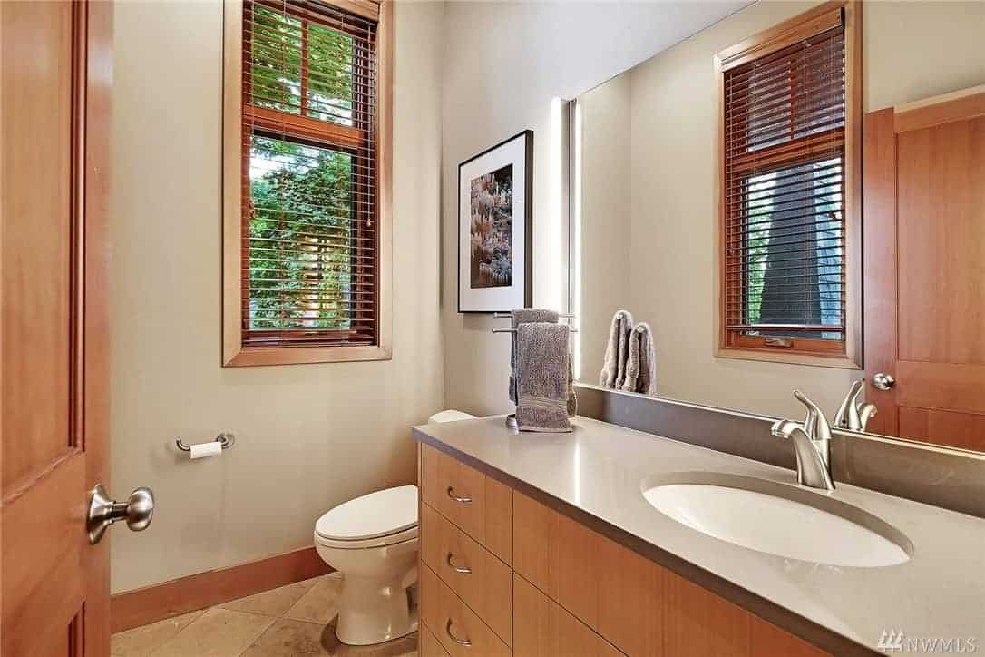 The white walls of this bathroom have a pair of tall windows that provide a wonderful view of nature outside. These windows have wooden frames that are perfectly matched to the built-in cabinets and drawers of the vanity area that has a gray countertop and backsplash.