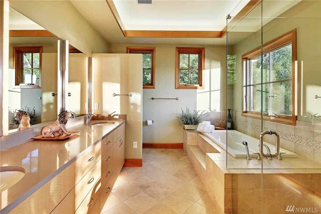 This Craftsman-Style bathroom has a brilliant white tray ceiling with a border of wood that matches the window frames. The marble flooring extends to the stone housing of the bathtub. Across from it is the vanity area that has two sinks topped with a wide wall-mounted mirror.