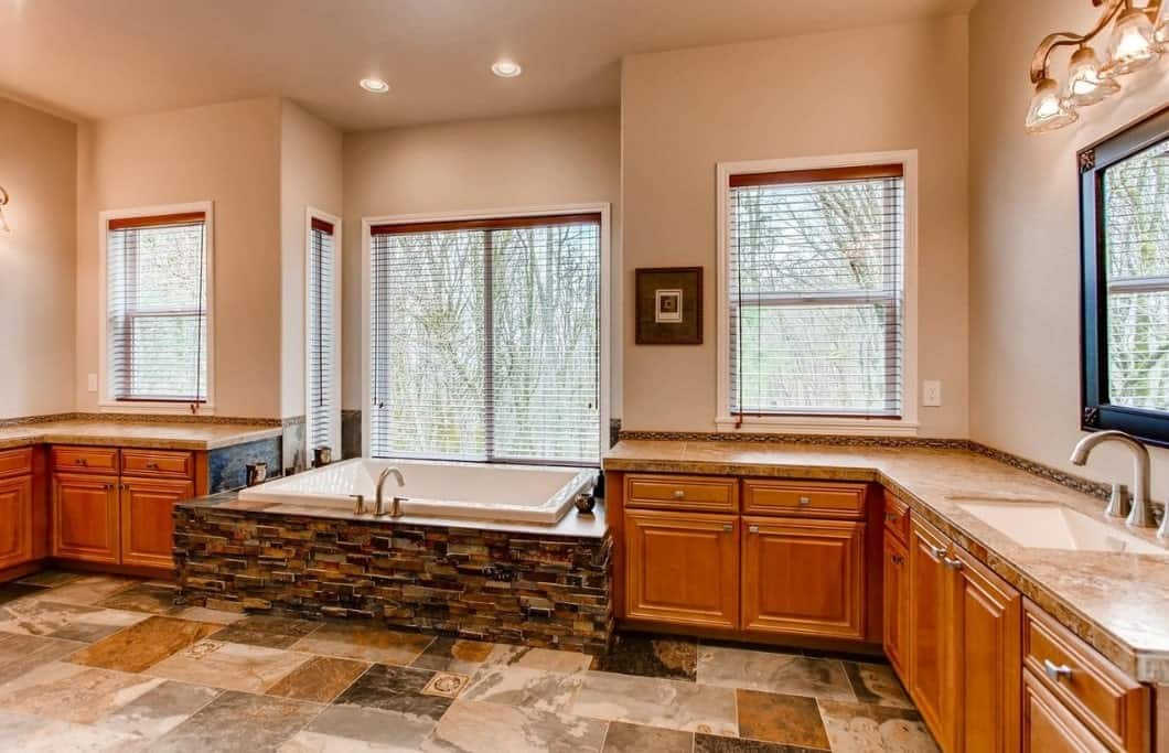 This is a charming and airy bathroom that has colorful marble flooring that extends to the stoneworks surrounding the bathtub. This bathtub is flanked by L-shaped peninsulas with marble countertop and built-in wooden drawers and cabinets.