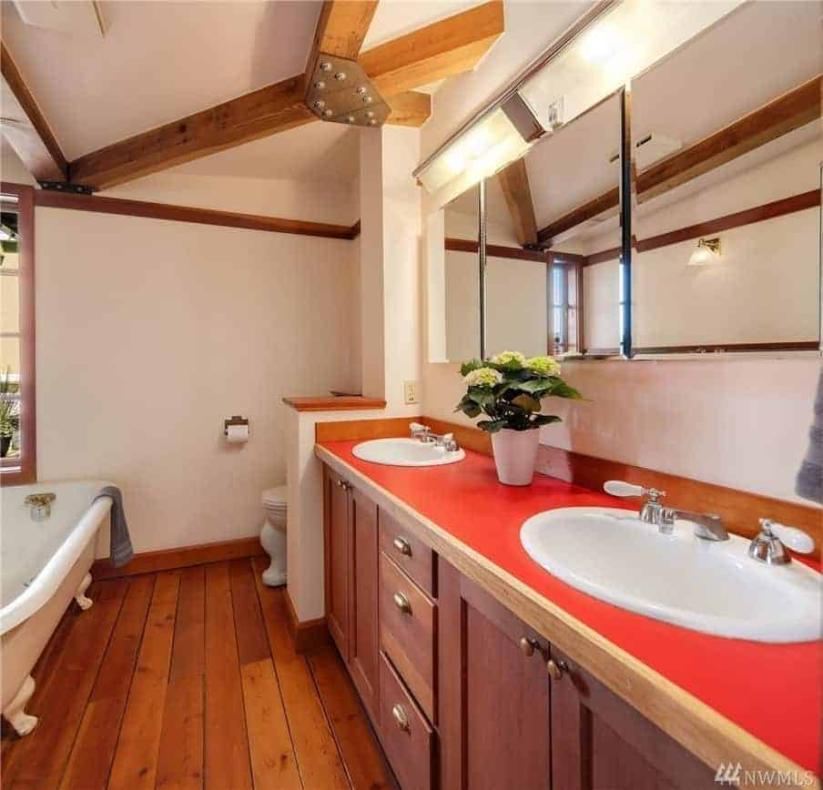 This Craftsman-Style bathroom has a stark red countertop to its vanity area that is fitted with built-in redwood cabinets and drawers that match the hardwood floor. The white ceiling has exposed wooden beams over the free-standing bathtub by the window.