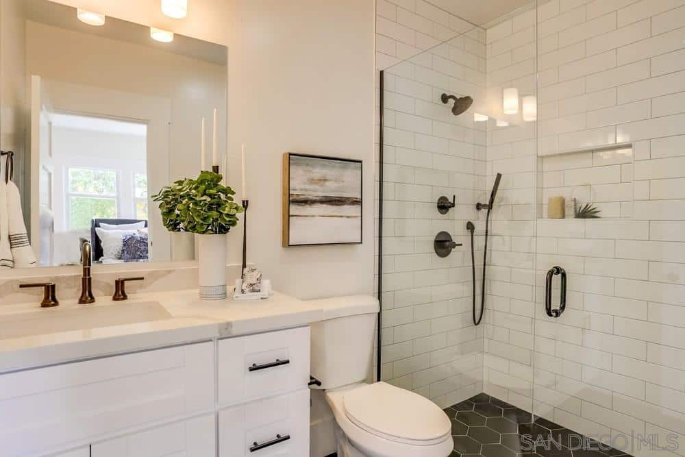 Dark hexagonal tiles run the floor of this bathroom that provides a nice contrast to the white-tiled walls and white vanity area that has an elegant brass faucet. This brass faucet contrasts the white marble countertop and backsplash and wall-mounted mirror.