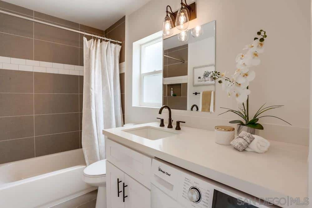 This small and simple bathroom has a vanity area that fitted built-in cabinets and a modern white clothes washer. The countertop of this vanity area is a white slab that contrasts with the brass faucet. The wall-mounted mirror is topped with rustic lamps that shine a warm yellow light.