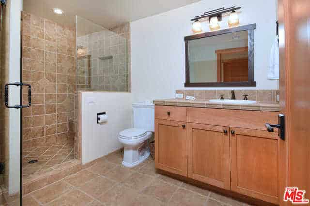 The beige tiles of the bathroom floor extend to the walls of the shower area that has a glass door. Those same tiles are also used for the countertop and backsplash of the faucet area that has a built-in wooden drawer and cabinets with a framed mirror mounted above.