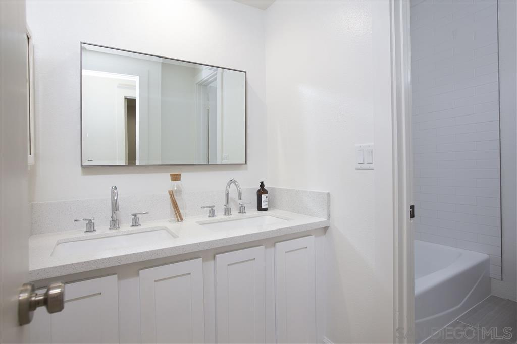 The white simplicity of this Craftsman-Style bathroom gives it a warm quality of homey comfort. Although small, the vanity area is able to accommodate two sinks with their own silver faucets. Above the sinks is a single wall-mounted rectangular mirror.