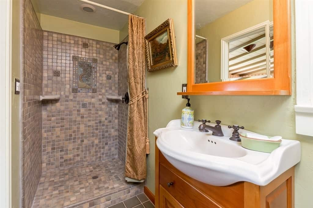 The random patterned small tiles of the shower area are adorned with a tiled artwork of a tree and provide separation to the rest of the bathroom. There is an elegantly framed painting mounted beside the mirror of the vanity area that has wooden drawers.