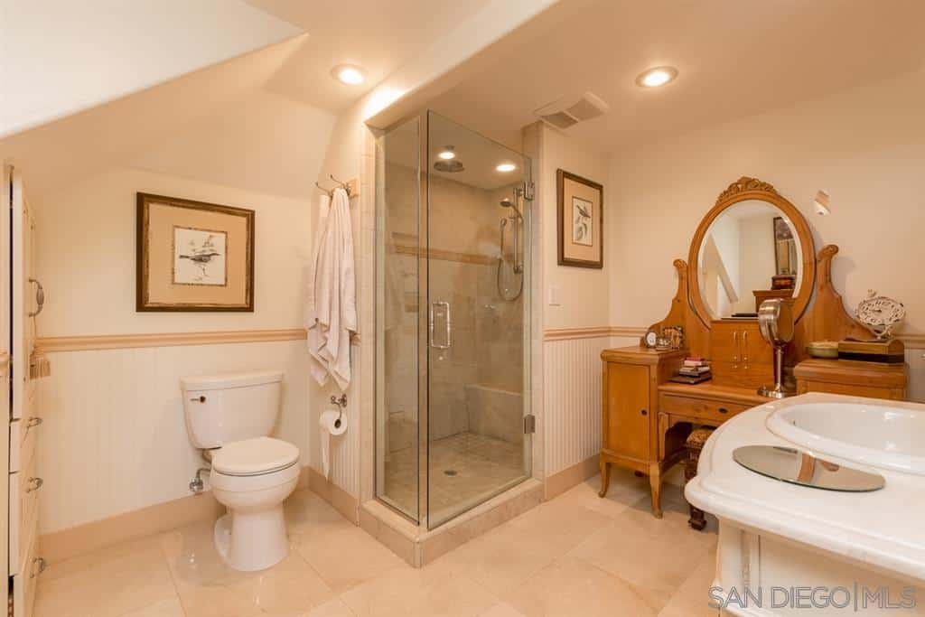 An intimate shower area is boxed in with a glass door that detaches it from the rest of the Craftsman-Style bathroom. The beige tiles of the floor match with the white walls and white ceiling fitted with pin lights. The stand-out element here is the wooden dresser that serves as a vanity area.