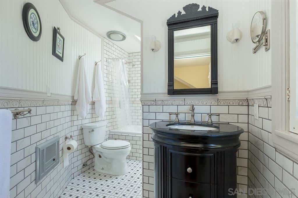 This Craftsman-Style bathroom has a brightness to it that is broken by the dark wood tone of the vanity area's built-in drawers that match the frames of the mirror and wall-mounted artworks. These artworks stand out against the white-tiled walls that are given a black grout finish.