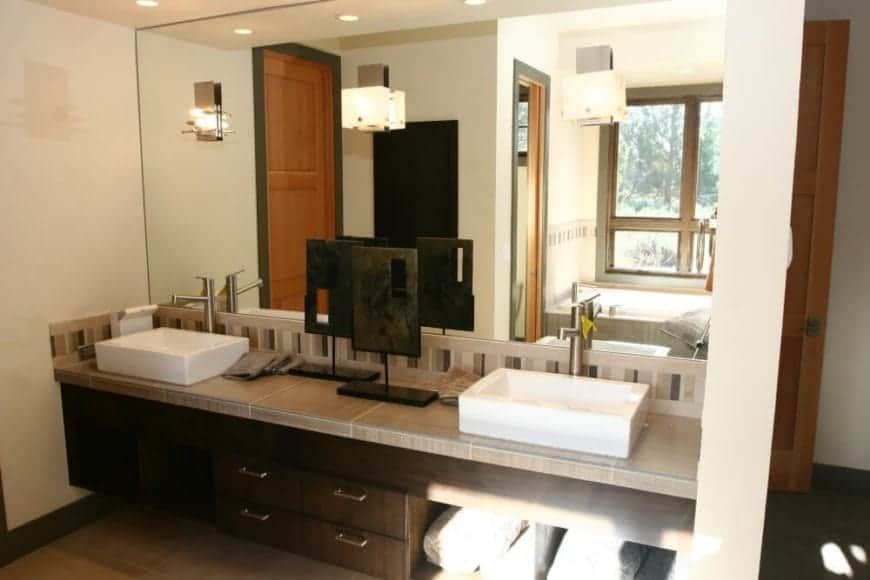 There are modern lamps mounted on the massive mirror that spans from the striped backsplash to the white ceiling that is lined with pin lights. They illuminate the beige countertop of the dual-sink vanity area that is adorned with a peculiar artwork.