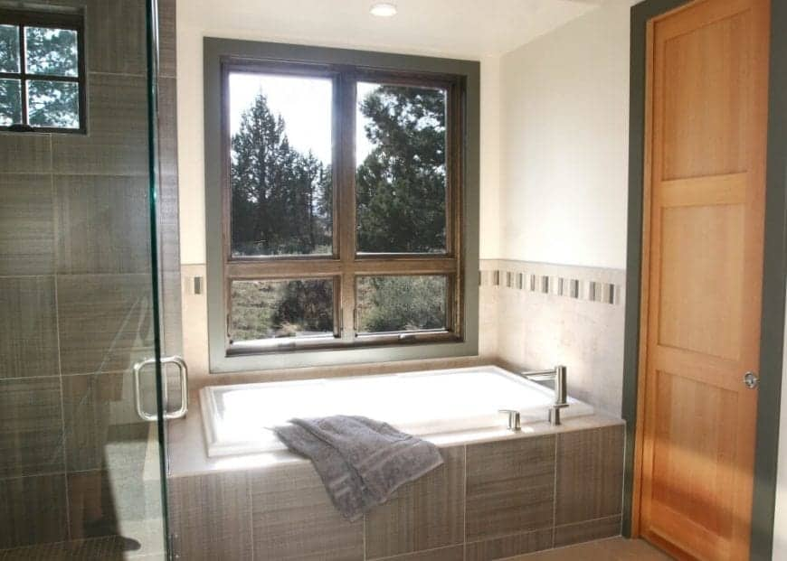 This Craftsman-Style bathroom has a massive window shining down on the bathtub. This bathtub is housed with gray tiles that pair well with the window frame and doorway. The white walls and ceiling are illuminated by the natural light coming from the window.