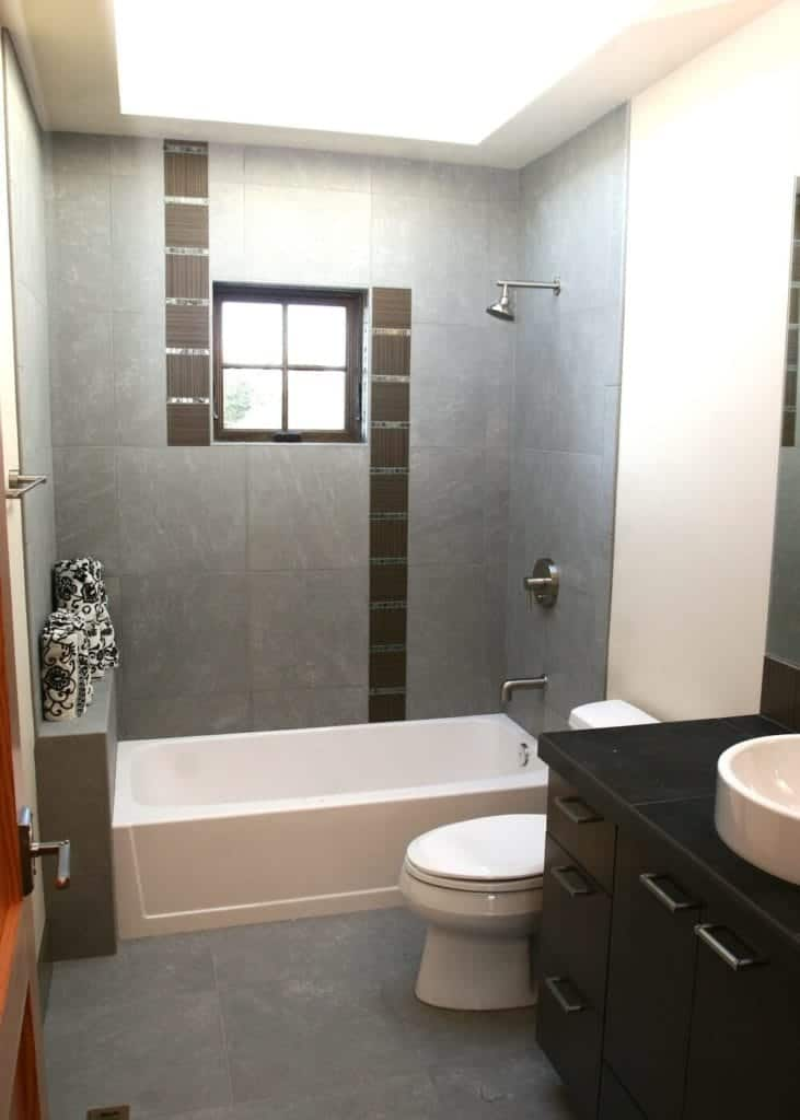 The brilliantly white tray ceiling contrasts with the gray walls and gray-tiled flooring. The gray hues emphasize the whiteness of the bathtub and toilet. On the other hand, the white sink stands out against the dark countertop of the vanity are and its built-in cabinets and drawers.