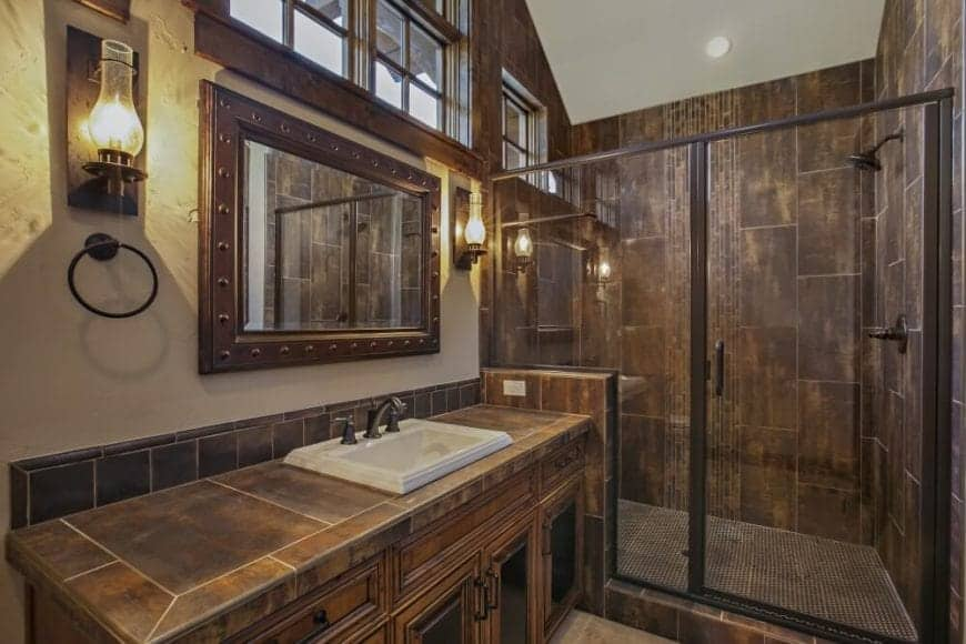 This Craftsman-Style bathroom has different shades of rust with its tiled walls, countertop and even the frame of the wall-mounted mirror that are adorned with iron studs. This mirror is flanked by a pair of rustic wall-mounted lamps and topped with windows.