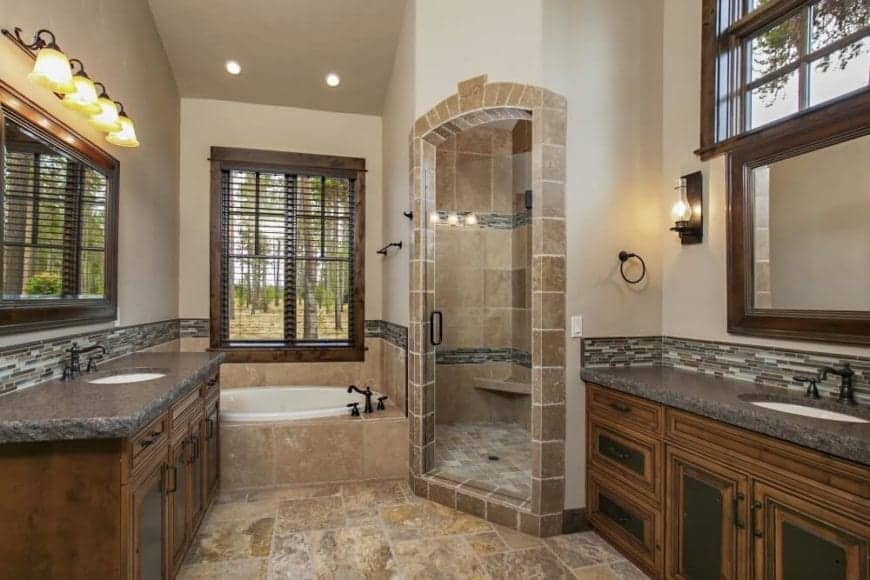 The circular bathtub is fitted into the wall with marble and a dark faucet. This tub area is given a wonderful view by the window above it. Beside it is a glass door that opens to the shower area. This bathroom has two vanity areas that are placed against the two walls that have wood-framed mirrors mounted above the faucets.