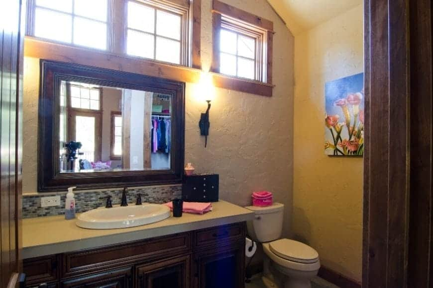 There is a beautiful wall-mounted painting of tulips that bring color to the textured beige walls of this Craftsman-Style bathroom. The beige walls serve as a good background for the dark wooden tones of the mirror and built-in cabinets of the vanity area.