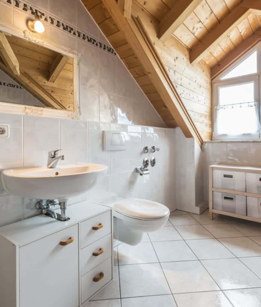 This Craftsman-Style bathroom is divided in two by the white and wooden tones of the wooden cathedral ceiling with exposed wooden beams. The white tiles on the floor and walls are emphasized by the natural light coming in from the windows.