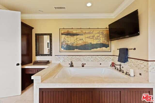 This bathroom has a comfortable and luxurious bathtub that is housed with marble that has a dark wood finish on its side that matches with the built-in drawers of the vanity area. The beige walls are accented with a wall-mounted painting and TV.