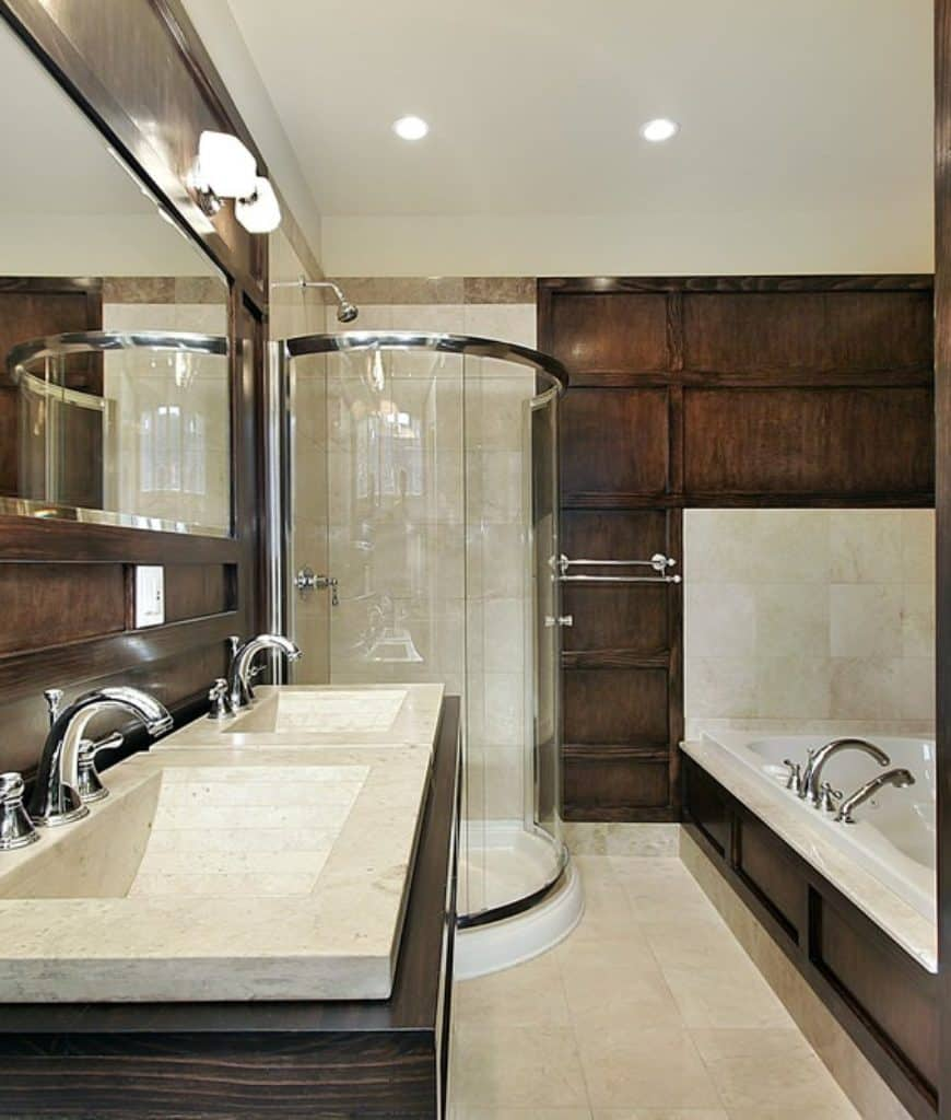 The shower area has a sleek circular glass enclosure that contrasts well with the elegant dark wood finish of the walls that match the sides of the bathtub housing and vanity area. The same dark wood finish frames the wall-mounted mirror above the faucets.