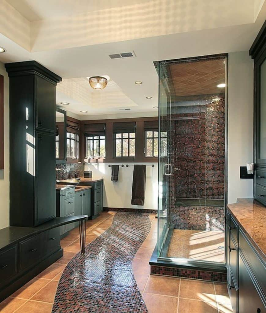 A charming walkway made up of colorful small tiles split the beige-tiled flooring in this Craftsman-Style bathroom. The colorful tiles match those of the shower area that is enclosed with glass. Elegant dark green wooden cabinets and drawers line the wall leading to the sink area.