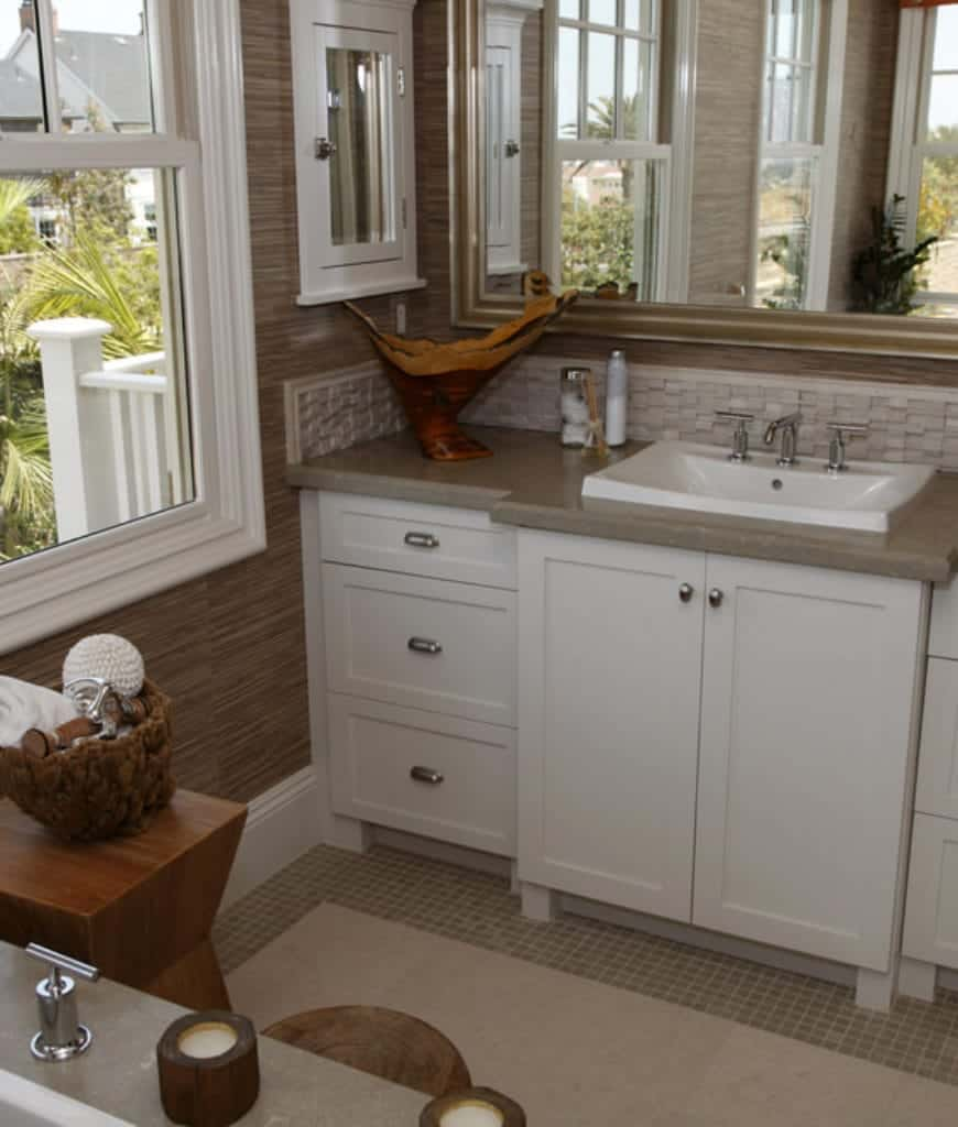 The bathroom's vanity area has a white sink that pairs well with the built-in cabinets and drawers with a gray countertop. This countertop has the same hue as the tiles of the floor that is topped with a white area rug. This makes the walls stand out with its wood-like wallpaper.