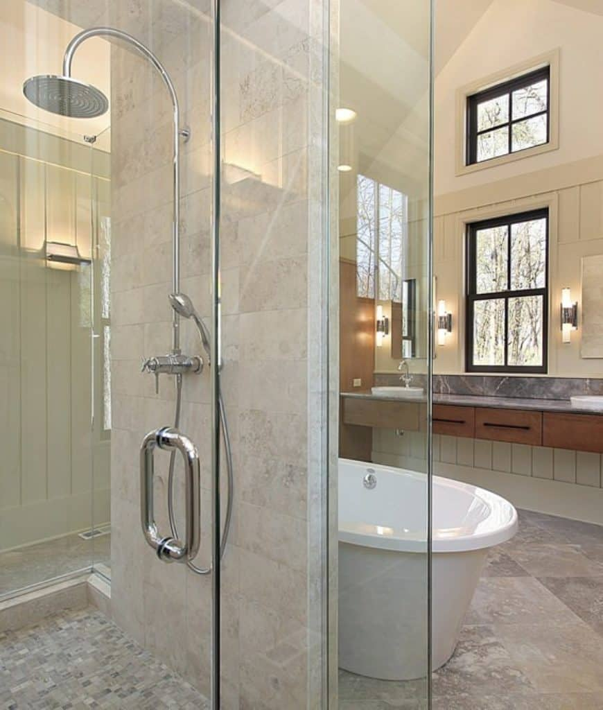 This Craftsman-Style bathroom has a shower area that is enclosed with glass and is separated from the bathtub with a wall that houses the modern shower fixtures. The white freestanding tub stands out against the wooden hues of the vanity area's drawers.