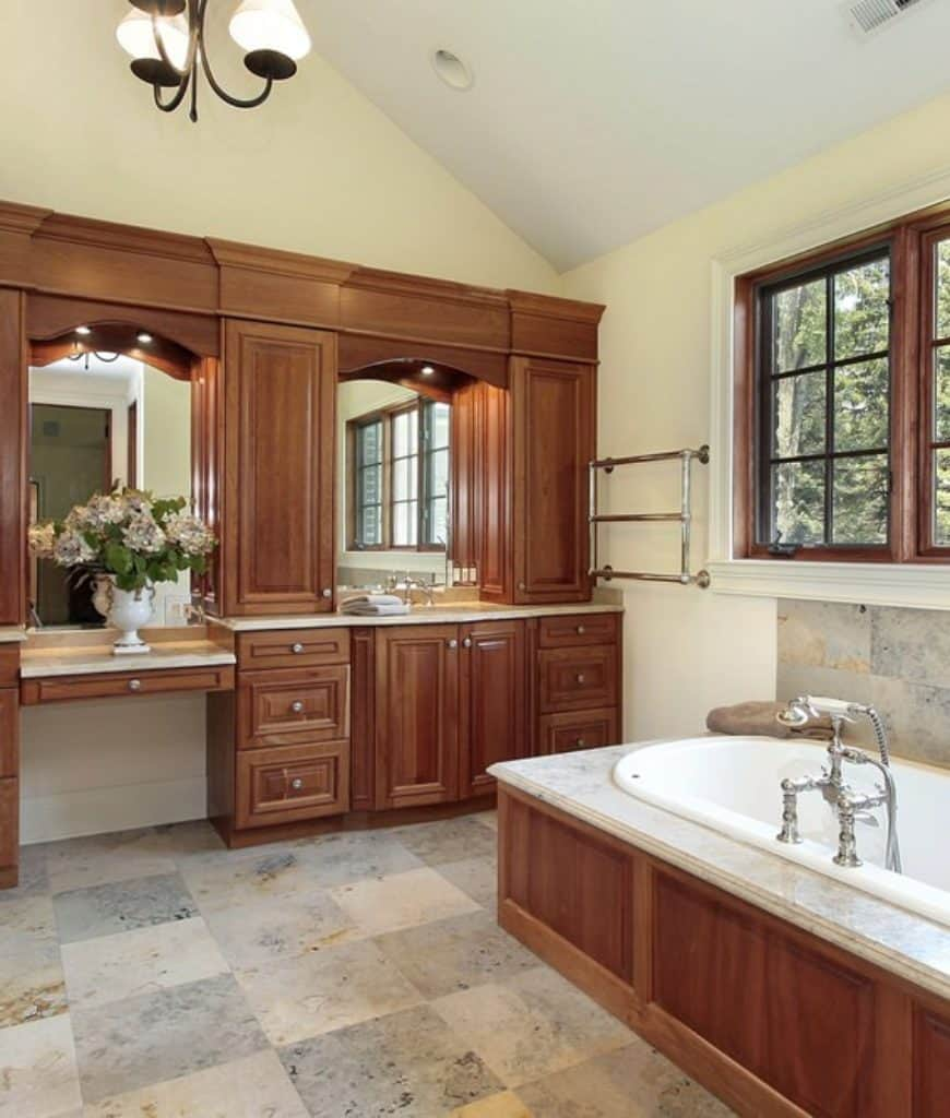 A massive wooden structure is placed against the wall opposite the bathtub. This structure holds the vanity area and has cabinets and drawers that match the wooden finish of the bathtub housing. Above the bathtub are French windows with wooden frames.
