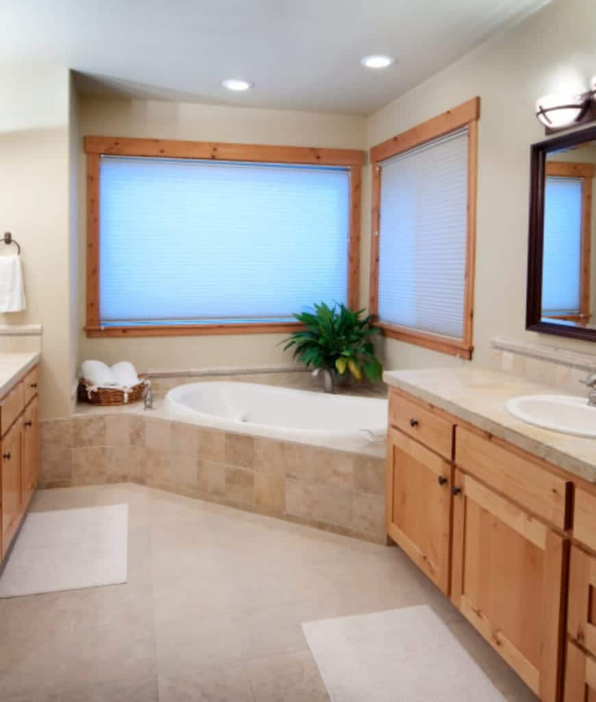 The bathtub is built into the corner of this Craftsman-Style bathroom with a marble housing. A pair of wood-framed windows fill the corners above the bathtub. The marble of the bathtub is used on the countertops of the vanity areas with wall-mounted mirrors above the faucet.