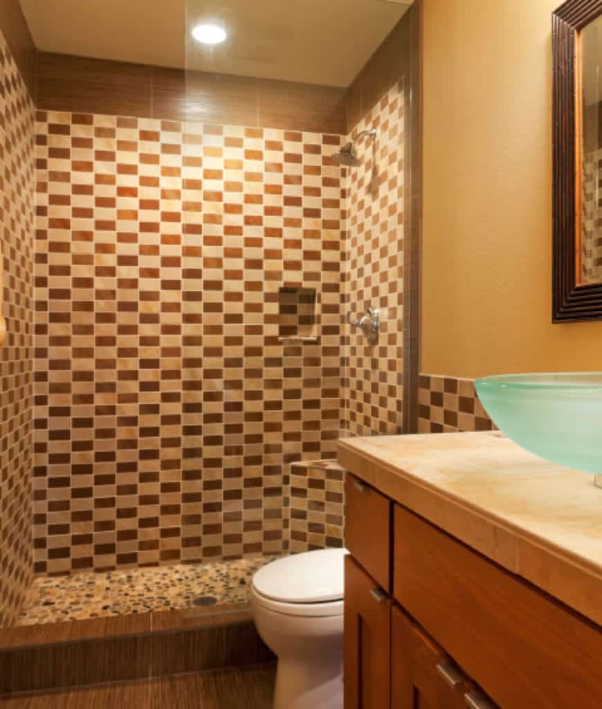 The shower area stands out in this bathroom with its tiles that form checkered patterns on its walls. This is illuminated by pin lights of the white ceiling that plays well with the beige walls of the rest of the bathroom. The floor has tiles that look like wood that goes well with the actual wood of the vanity area's cabinets topped with a crystal sink.