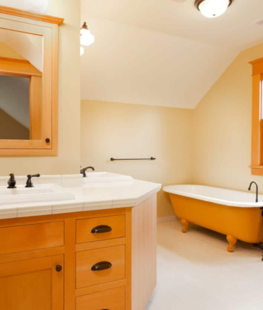 The freestanding bathtub of this Craftsman-Style bathroom is painted with a yellowish wooden hue that matches the built-in cabinets and drawers of the sink and the frames of the window. The sink is given an L-shaped peninsula that follows the lay of the walls.