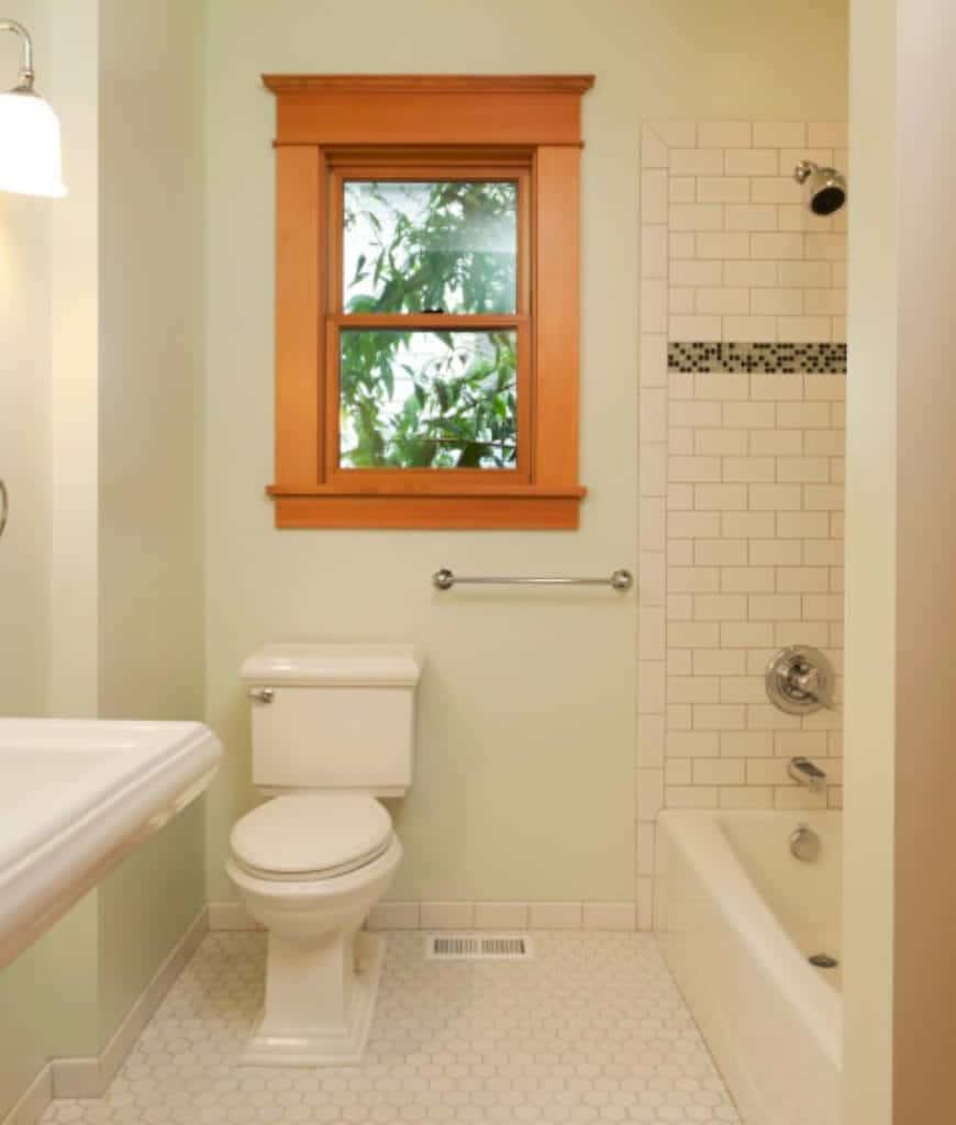 This is a simple and traditional Craftsman-Style bathroom with its white hexagonal floor tiles and white tiles of the bathtub that doubles as a shower area. The white bathtub matches with the white toilet and sink. The stand-out element here is the wood-framed window against the light-hued walls.
