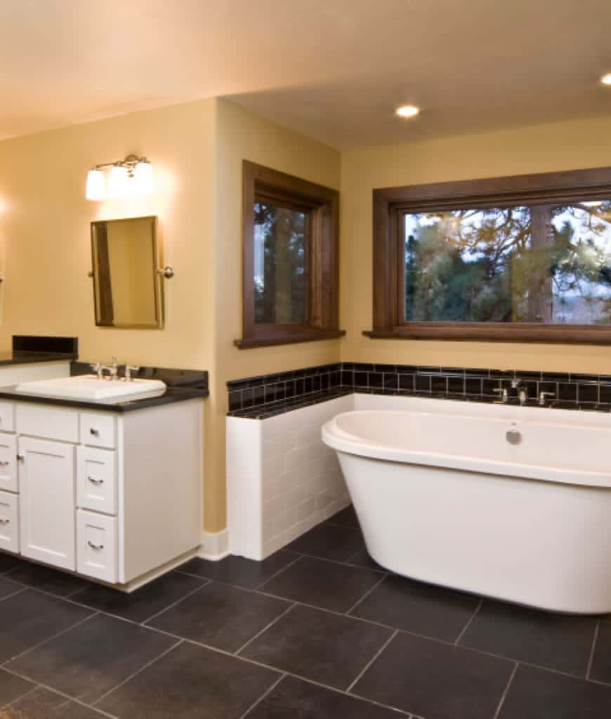 The white ceiling contrasts well with the dark tiles of the floor. These dark tiles match the countertop of the sink area and the tiles surrounding the freestanding bathtub which is surrounded by wide windows that are framed with dark wood.